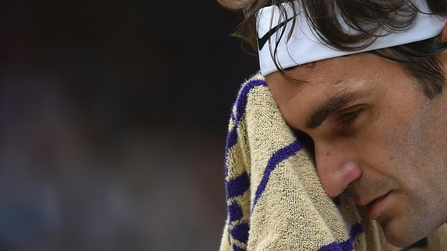 Roger Federer of Switzerland wipes his face with a towel during the men's singles final against Novak Djokovic of Serbia at the All England Lawn Tennis Championships in Wimbledon, London, Sunday July 12, 2015. (Toby Melville/Pool Photo via AP)