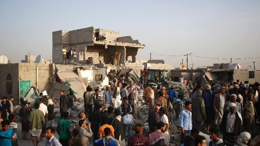 People gather at the site of houses destroyed by Saudi airstrikes in Sanaa, Yemen, Monday, July 13, 2015. Airstrikes by the Saudi-led coalition targeting Shiite rebels and their allies struck several Yemeni cities on Sunday, with combat raging near the strategic Bab el-Mandeb strait despite a declared truce, military and security officials said. (AP Photo/Hani Mohammed)