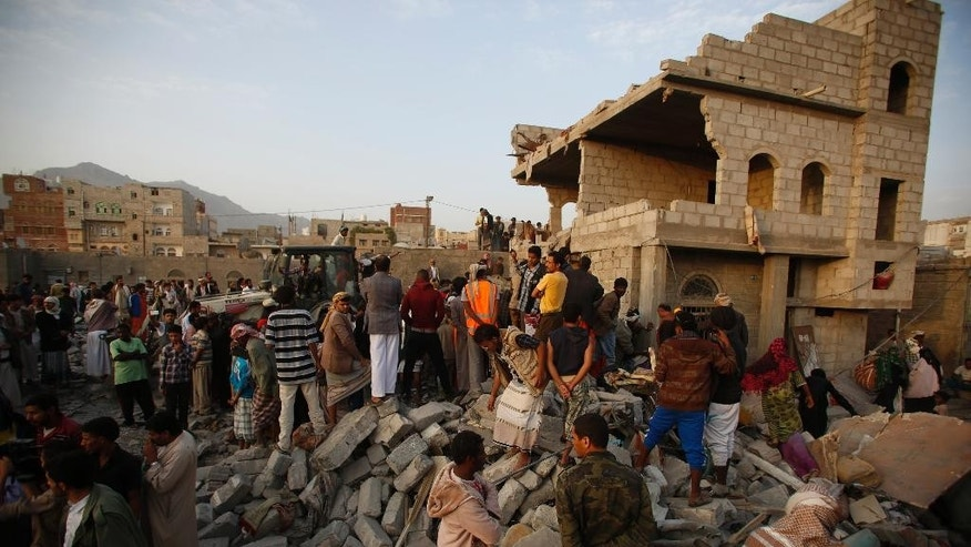 People search for survivors under the rubble of houses destroyed by Saudi airstrikes in Sanaa, Yemen, Monday, July 13, 2015. Airstrikes by the Saudi-led coalition targeting Shiite rebels and their allies struck several Yemeni cities on Sunday, with combat raging near the strategic Bab el-Mandeb strait despite a declared truce, military and security officials said. (AP Photo/Hani Mohammed)