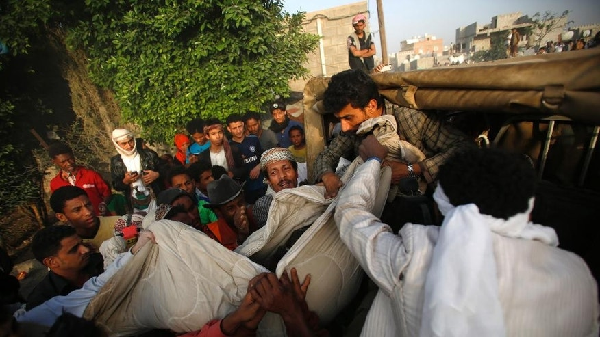 People carry the body of a man they uncovered from under the rubble of houses destroyed by Saudi-led airstrikes in Sanaa, Yemen, Monday, July 13, 2015. Airstrikes by the Saudi-led coalition targeting Shiite rebels and their allies struck several Yemeni cities on Sunday, with combat raging near the strategic Bab el-Mandeb strait despite a declared truce, military and security officials said. (AP Photo/Hani Mohammed)