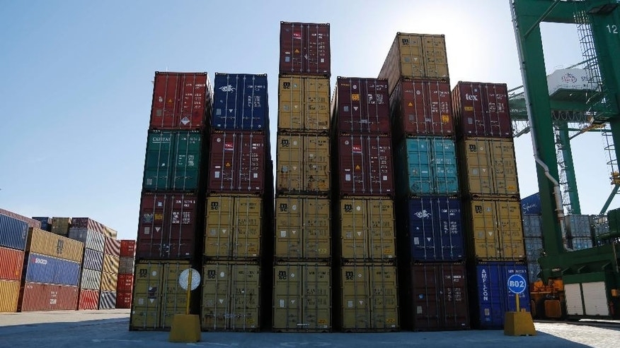 Containers lay stacked at the port in the Bay of Mariel, Cuba, Monday, July 13, 2015. With Mariel, Cuba is looking ahead to when the U.S. embargo may be lifted as part of a rapprochement begun by presidents Barack Obama and Raul Castro in December. Washington and Havana plan to officially restore diplomatic relations on Monday. (AP Photo/Desmond Boylan)