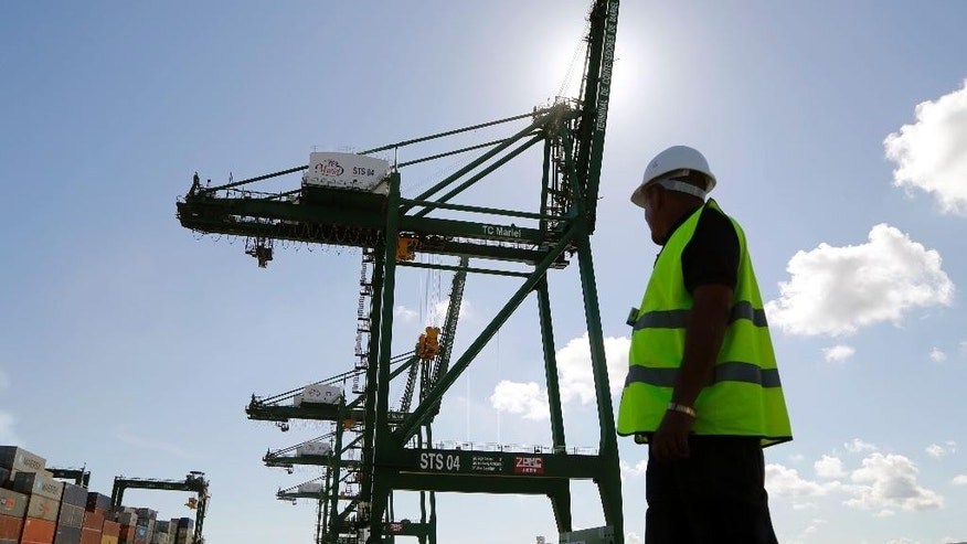 A worker stands near a crane at the container terminal at the port in the Bay of Mariel, Cuba, Monday, July 13, 2015. Not far from this port, workers have finished grading a flat area the size of a football field for the first private companies to establish operations in a special economic development zone billed as a key part of the country's effort to attract foreign investment and jumpstart a sluggish economy. (AP Photo/Desmond Boylan)