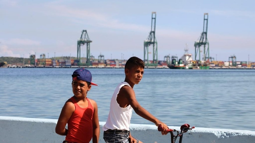 Youth pause on the opposite side of a port's container terminal in the Bay of Mariel, Cuba, Monday, July 13, 2015. Mariel bay is being dredged to accommodate deeper-drafting ships than those that can use the port of Havana, which cannot be expanded because of an automobile tunnel that traverses its mouth. (AP Photo/Desmond Boylan)