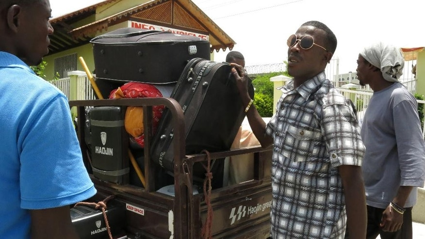 In this June 25, 2015 photo, farm worker Felix Babe, right, loads his luggage on a motorcycle taxi at the Dominican-Haitian border in Ouanaminthe, Haiti, as he returns voluntarily to his native Haiti after living nine years in the DR. The end of a year-long application period has sparked an exodus to Haiti of people who failed to qualify and are now seeking either to wait out what they fear could be a wave of mass deportations or to start uncertain new lives on the poorer side of Hispaniola. (AP Photo/Ezequiel Abiu Lopez)