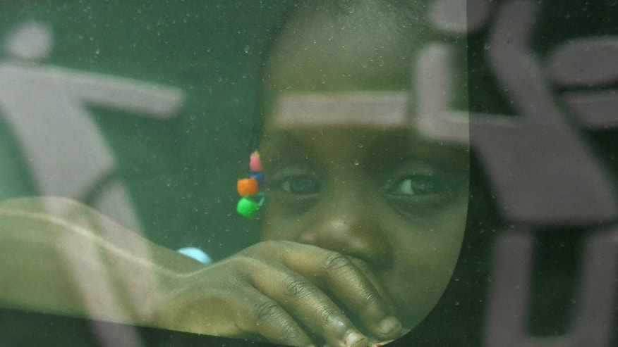 In this June 29, 2015 photo, a girl born in the Dominican Republic to Haitian parents peers through the window of a government car that will transport her and her family to the border with Haiti, in Santo Domingo, as her family returns voluntarily to their native Haiti after living in the DR several years. Many now traveling to Haiti say they are driven by fear of the violent, often traumatic expulsions that have occurred periodically in the Dominican Republic in the past, as well as frustration with an immigration program that requires documents that many cannot obtain. (AP Photo/Ezequiel Abiu Lopez)