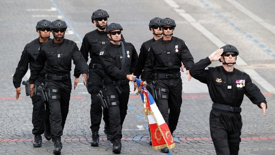French anti-terrorist forces parade on the Champs-Elysees avenue in Paris, France, as part of Bastille Day parade Tuesday, July 14, 2015. French anti-terrorist forces join the traditional military parade celebrating Bastille Day, as the country's leadership tries to show its muscle against extremists abroad and at home. Mexico's president is the guest of honor at this year's event marking France's biggest holiday. (AP Photo/Michel Euler)