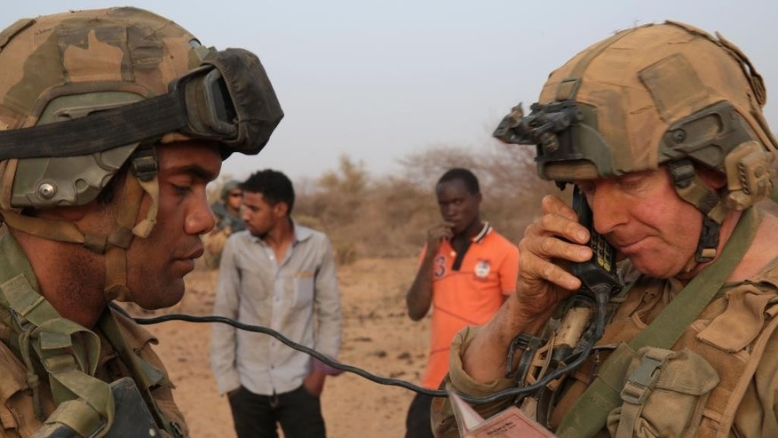 In this photo taken Sunday, June 21, 2015, a French soldier radios in the details of a man, left rear, taken from his driving license  in the desert south of the village of  Deliman, Mali. The fight against extremists in northern Mali has shifted from full on combat to a phase of hide-and-seek with jihadists, who are outnumbered and avoid direct contact with French troops, the forces say.  (AP Photo/Maeva Bambuck)