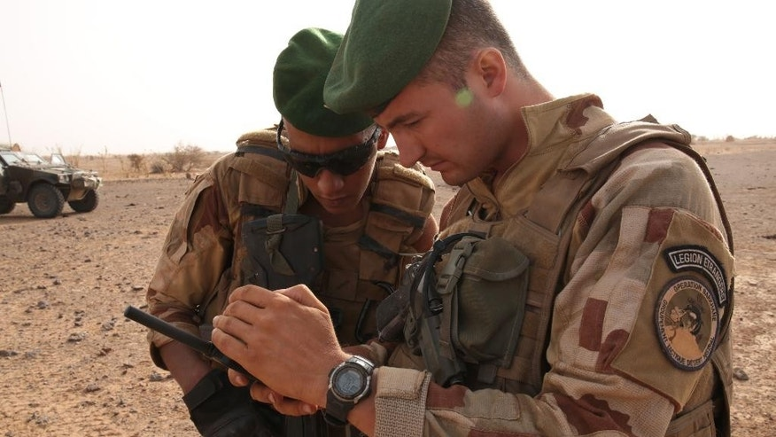 In this photo taken Sunday, June 21, 2015, French soldiers look at their sat phone as they are on patrol  in the desert south of the village of  Deliman, Mali. The fight against extremists in northern Mali has shifted from full on combat to a phase of hide-and-seek with jihadists, who are outnumbered and avoid direct contact with French troops, the forces say.  (AP Photo/Maeva Bambuck)