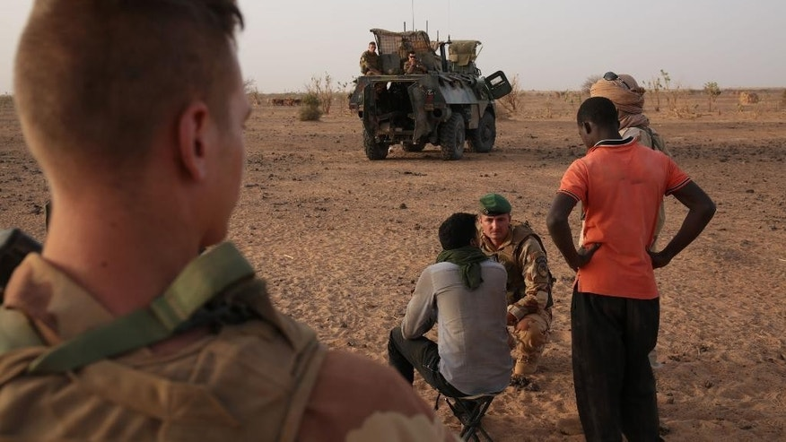 In this photo taken Sunday, June 21, 2015, a French soldier, rear third left,  speaks to a man, rear second left,  suspected of having links with extremists  in the desert south of the village of  Deliman,  Mali. The fight against extremists in northern Mali has shifted from full on combat to a phase of hide-and-seek with jihadists, who are outnumbered and avoid direct contact with French troops, the forces say. (AP Photo/Maeva Bambuck0