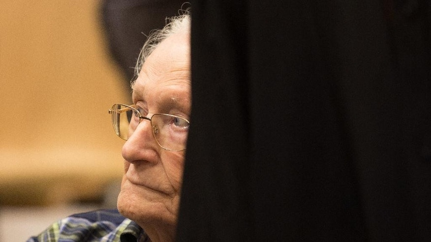 Former Auschwitz guard Oskar Groening, second left, sits in a courtroom prior to the start of his trial in Lueneburg, northern Germany, Tuesday, July 14, 2015. The 94-year-old former SS sergeant who served in Auschwitz said he helped the death camp function in his role sorting cash and valuables seized from Jews after they arrived in cattle-cars. (Axel Heimken/Pool Photo via AP)