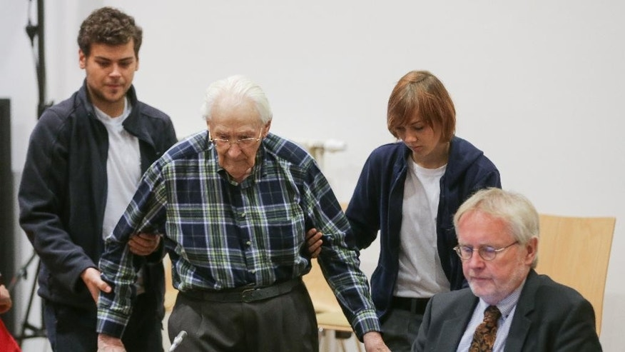 Former Auschwitz guard Oskar Groening, second left, is being led into a courtroom in Lueneburg, northern Germany, Tuesday, July 14, 2015. The 94-year-old former SS sergeant who served in Auschwitz said he helped the death camp function in his role sorting cash and valuables seized from Jews after they arrived in cattle-cars. (Axel Heimken/Pool Photo via AP)
