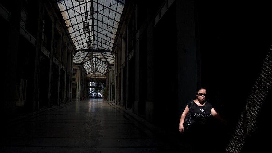 A woman passes an arcade with shutter shops in central Athens, Tuesday, July 14, 2015. The experts say Greece has largely failed in previous crackdowns on tax evasion, which has been rampant for generations. An estimated euro10 billion  in taxes never makes it into government coffers annually. (AP Photo/Petros Giannakouris)