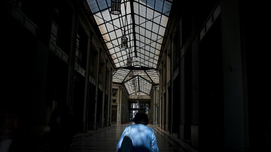 A man passes through an arcade with shuttered shops in central Athens, Tuesday, July 14, 2015. The experts say Greece has largely failed in previous crackdowns on tax evasion, which has been rampant for generations. An estimated 10 billion euros in taxes never makes it into government coffers annually. (AP Photo/Petros Giannakouris)