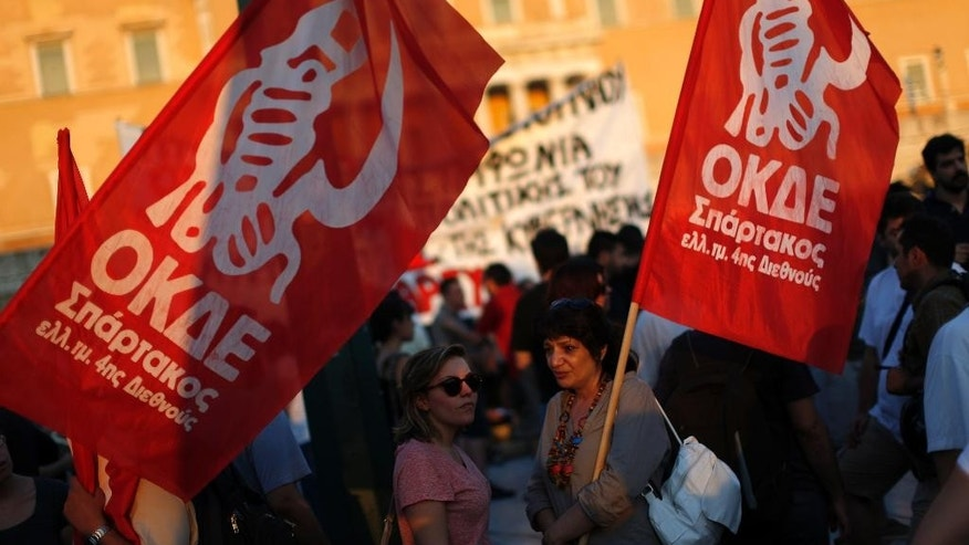 Anti-austerity protesters hold flags of their left-wing party during a rally against the government's agreement with its creditors in front of the Greek Parliament in Athens, Monday, July 13, 2015. After months of acrimony, Greece clinched a preliminary bailout agreement with its European creditors on Monday that will, if implemented, secure the country's place in the euro and help it avoid financial collapse. (AP Photo/Emilio Morenatti)