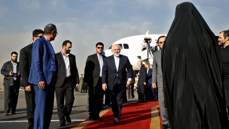Iran's Foreign Minister Mohammad Javad Zarif, who is also Iran's top nuclear negotiator, center, arrives at Mehrabad airport in Tehran, Iran, Wednesday, July 15, 2015. Zarif and his entourage returned to Tehran on Wednesday morning, a day after Iran and the West reached a historic nuclear deal. (AP Photo/Ebrahim Noroozi)
