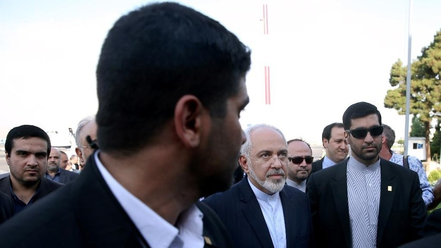 Iran's Foreign Minister Mohammad Javad Zarif, who is also Iran's top nuclear negotiator, center, arrives to Mehrabad airport in Tehran, Iran, Wednesday, July 15, 2015. Zarif and his entourage returned to Tehran on Wednesday morning, a day after Iran and the West reached a historic nuclear deal. (AP Photo/Ebrahim Noroozi)