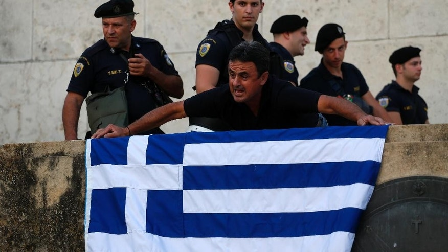 An anti-austerity protester places a Greek flag next to riot policemen as they guard one of the entrances of the Greek Parliament during a rally against the government's agreement with its creditors in Athens, Monday, July 13, 2015. After months of acrimony, Greece clinched a preliminary bailout agreement with its European creditors on Monday that will, if implemented, secure the country's place in the euro and help it avoid financial collapse. (AP Photo/Emilio Morenatti)
