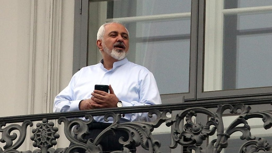 Iranian Foreign Minister Mohammad Javad Zarif talks to journalist from a balcony of the Palais Coburg where closed-door nuclear talks with Iran continue in Vienna, Austria, Monday, July 13, 2015. (AP Photo/Ronald Zak)