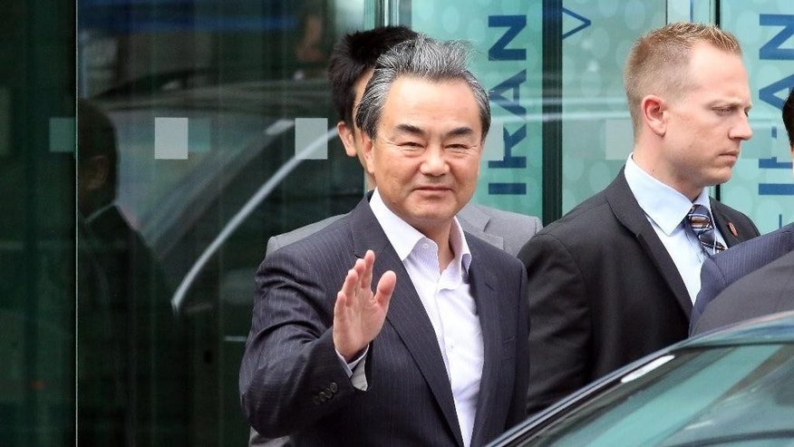 Chinese Foreign Minister Wang Yi, left, leaves Palais Coburg where closed-door nuclear talks with Iran continue in Vienna, Austria, Monday, July 13, 2015. (AP Photo/Ronald Zak)