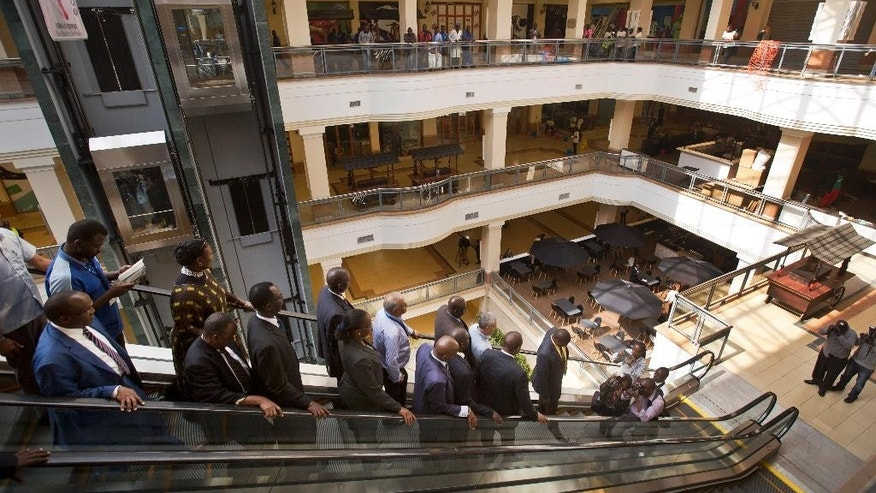 Kenyan dignitaries take a tour of the Westgate Mall, during a viewing for the media prior to it being re-opened to the public, in Nairobi, Kenya Tuesday, July 14, 2015. Kenyan officials say the city's Westgate Mall will re-open Saturday, nearly two years after an attack there on Sept. 21, 2013 by al-Shabab extremists left at least 67 people dead and led to a four-day siege by security forces. (AP Photo/Ben Curtis)