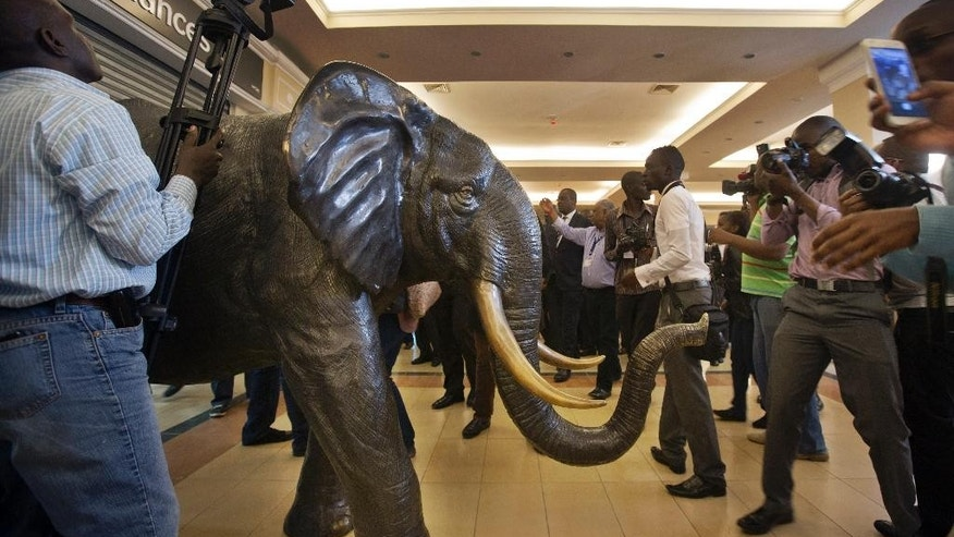 A cameraman films over a statue of an elephant, the symbol of the supermarket chain Nakumatt, as media follow Nairobi Governor Evans Kidero on a tour of Westgate Mall, during a viewing for the media prior to it being re-opened to the public, in Nairobi, Kenya Tuesday, July 14, 2015. Kenyan officials say the city's Westgate Mall will re-open Saturday, nearly two years after an attack there on Sept. 21, 2013 by al-Shabab extremists left at least 67 people dead and led to a four-day siege by security forces. (AP Photo/Ben Curtis)