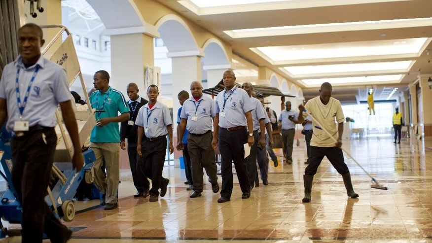 Employees of the supermarket chain Nakumatt walk towards the shop as a worker cleans the floors of the Westgate Mall with a mop, during a viewing for the media prior to it being re-opened to the public, in Nairobi, Kenya Tuesday, July 14, 2015. Kenyan officials say the city's Westgate Mall will re-open Saturday, nearly two years after an attack there on Sept. 21, 2013 by al-Shabab extremists left at least 67 people dead and led to a four-day siege by security forces. (AP Photo/Ben Curtis)