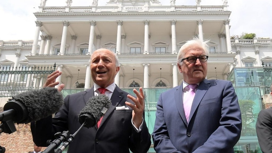 French Foreign Minister Laurent Fabius and German Foreign Minister Frank-Walter Steinmeier, from left, brief the media in front of Coburg where closed-door nuclear talks with Iran continue in Vienna, Austria, Monday, July 13, 2015. (AP Photo/Ronald Zak)