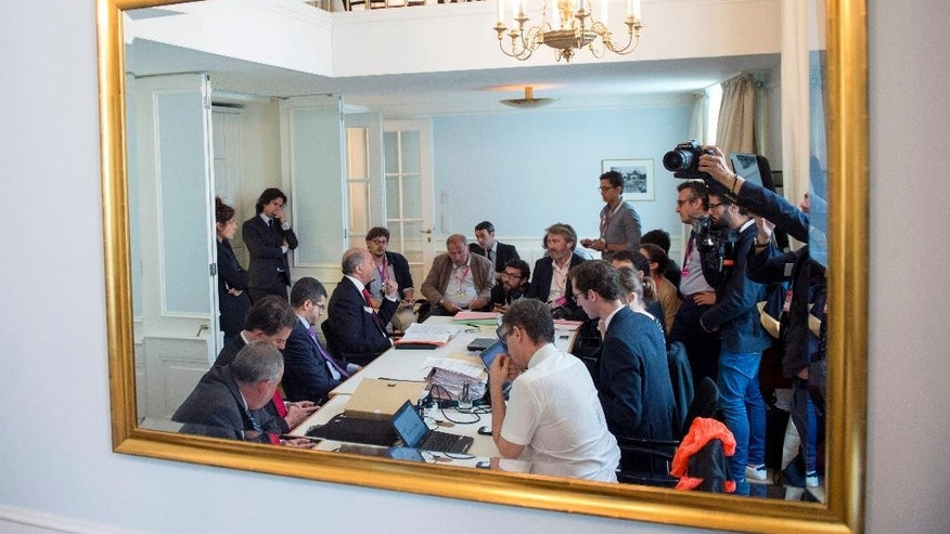 French Foreign Minister Laurent Fabius, sitting fourth left, briefs French journalists at the Palais Coburg Hotel, where the Iran nuclear talks are being held, in Vienna, Austria, Tuesday, July 14, 2015. After 18 days of intense and often fractious negotiation, diplomats Tuesday declared that world powers and Iran had struck a landmark deal to curb Iran's nuclear program in exchange for billions of dollars in relief from international sanctions, an agreement designed to avert the threat of a nuclear-armed Iran and another U.S. military intervention in the Muslim world. (Joe Klamar/Pool Photo via AP)