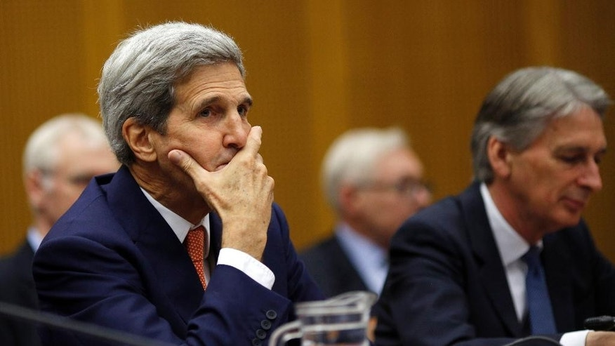 U.S. Secretary of State John Kerry gestures as he sits next to British Foreign Secretary Philip Hammond, at a plenary session at the United Nations building in Vienna, Austria, Tuesday,  July 14, 2015. After 18 days of intense and often fractious negotiation, world powers and Iran struck a landmark deal Tuesday to curb Iran's nuclear program in exchange for billions of dollars in relief from international sanctions — an agreement designed to avert the threat of a nuclear-armed Iran and another U.S. military intervention in the Muslim world. (Carlos Barria, Pool Photo via AP)