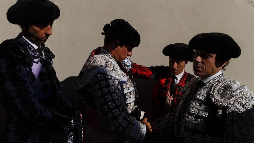 Spanish bullfighter Julian Lopez 'El Juli' , center, adjusts his cape while waits to do the 'paseillo' or ritual entrance to the arena before a bullfight of the San Fermin festival in Pamplona, Spain, Monday, July 13, 2015. Revelers from around the world arrive in Pamplona every year to take part in some of the eight days of party and the running of the bulls. (AP Photo/Daniel Ochoa de Olza)
