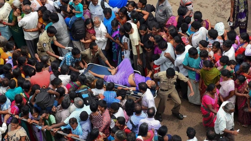 A woman is rushed to a hospital on a stretcher after a stampede during a Hindu religious bathing festival on the bank of the Godavari River in Rajahmundry, Andhra Pradesh state, India, Tuesday, July 14, 2015. The stampede occurred as tens of thousands of people pushed forward to bathe in the river on the first day of the Pushkaralu festival, an official said.  (AP Photo/ Ramana)