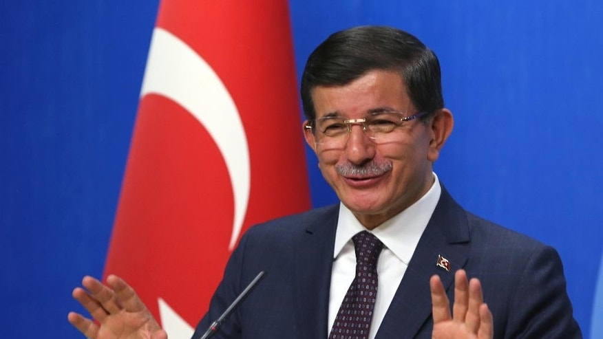 Turkish Prime Minister and leader of Justice and Development Party Ahmet Davutoglu speaks to the media after a meeting with Kemal Kilicdaroglu, the leader of the main opposition Republican People's Party, CHP, in Ankara, Turkey, Monday, July 13. 2015.  Davutoglu has begun a first round of talks on forming a coalition government by meeting officials of Turkey's secularist party, CHP,  his ruling Islamic-rooted party's arch-foe. Davutoglu met with Kilicdaroglu on Monday, a month after Turkey's June 7 election left his party short of a majority, forcing it to seek a coalition alliance.(AP Photo/Burhan Ozbilici)