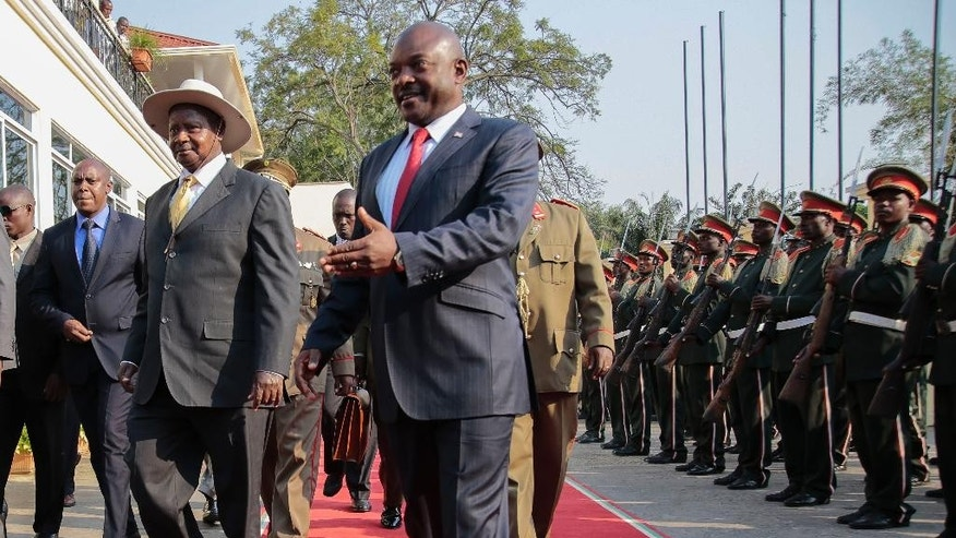 President of Uganda Yoweri Museveni, left, is welcomed by the President of Burundi, Pierre Nkurunzira, centre, in Bujumbura, Burundi, Tuesday, July 14, 2015. Uganda's president has started mediating talks between Burundi's government and opposition groups that are opposed to President Pierre Nkurunziza's controversial bid for a third term. (AP Photo/Berthier Mugiraneza)