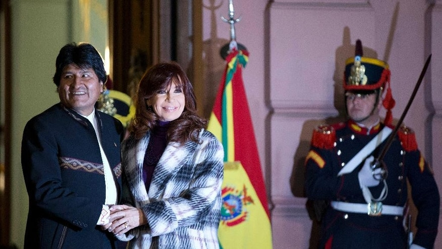 Bolivia's President Evo Morales and Argentina's Cristina Fernandez hold hands as they wait to unveil a bronze statue of Bolivian war of independence heroine Juana Azurduy de Padilla, behind the government house in Buenos Aires, Argentina, Wednesday, July 15, 2015.  The statue is a present from Bolivia and replaces a statue of Christopher Columbus brought down in 2013. (AP Photo/Natacha Pisarenko)