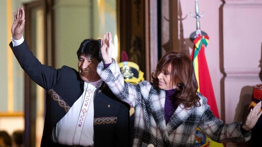 Bolivia's President Evo Morales and Argentina's Cristina Fernandez wave to supporters as they wait to unveil a bronze statue of Bolivian war of independence heroine Juana Azurduy de Padilla, behind the government house in Buenos Aires, Argentina, Wednesday, July 15, 2015.  The statue is a present from Bolivia and replaces a statue of Christopher Columbus brought down in 2013. (AP Photo/Natacha Pisarenko)