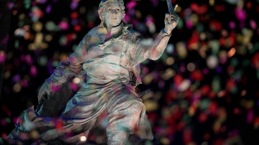 Confetti rains on the newly unveiled statue of Bolivian Juana Azurduy de Padilla, behind the government house in Buenos Aires, Argentina, Wednesday, July 15, 2015. The presidents of Argentina and Bolivia led the ceremony of the unveiling of the statue of the Bolivian war of independence heroine. The statue is a present from Bolivia and replaces a statue of Christopher Columbus brought down in 2013.  (AP Photo/Natacha Pisarenko)