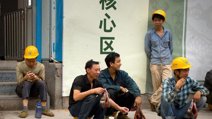 Construction workers take a break outside of a construction site in Beijing, Wednesday, July 15, 2015. China's economic growth in the latest quarter held steady at 7 percent, its weakest performance since the global crisis, but better retail sales and factory output in June suggested efforts to reverse the slump might be gaining traction. (AP Photo/Mark Schiefelbein)
