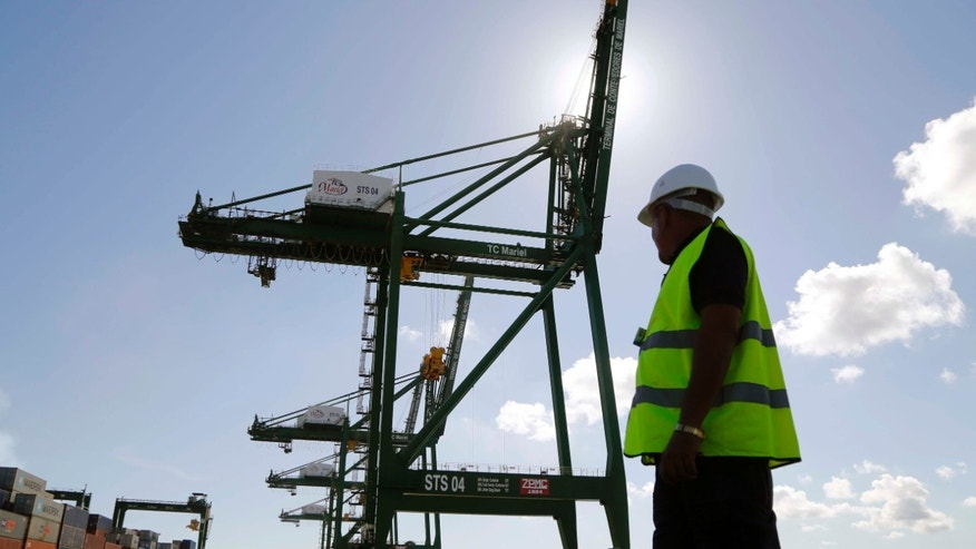 A worker stands near a crane at the container terminal at the port in the Bay of Mariel, Cuba, Monday, July 13, 2015.