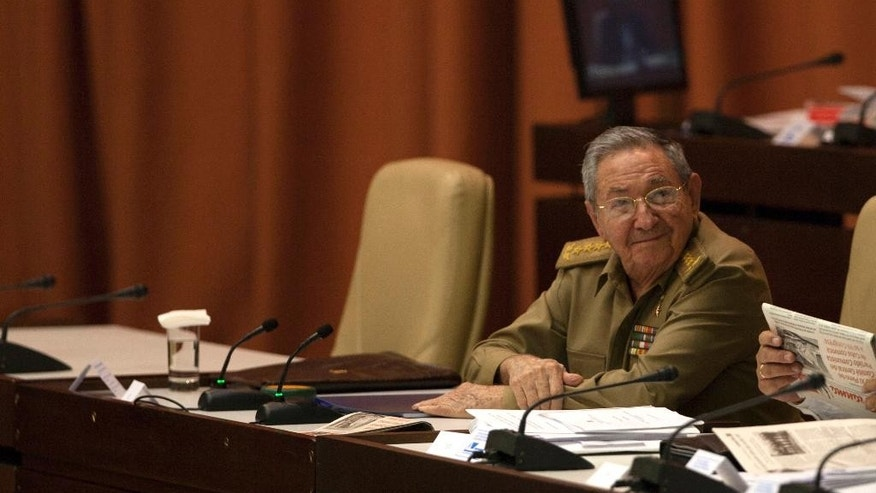Cuba's President Raul Castro attends a National Assembly session, as he sits next to the chair that Fidel Castro always used, left empty, in Havana, Cuba, Wednesday, July 15, 2015. The parliament is holding one of its twice-annual regular sessions with a new twist: It's live-tweeting the proceedings for the first time. (AP Photo/Ismael Francisco, Cubadebate)