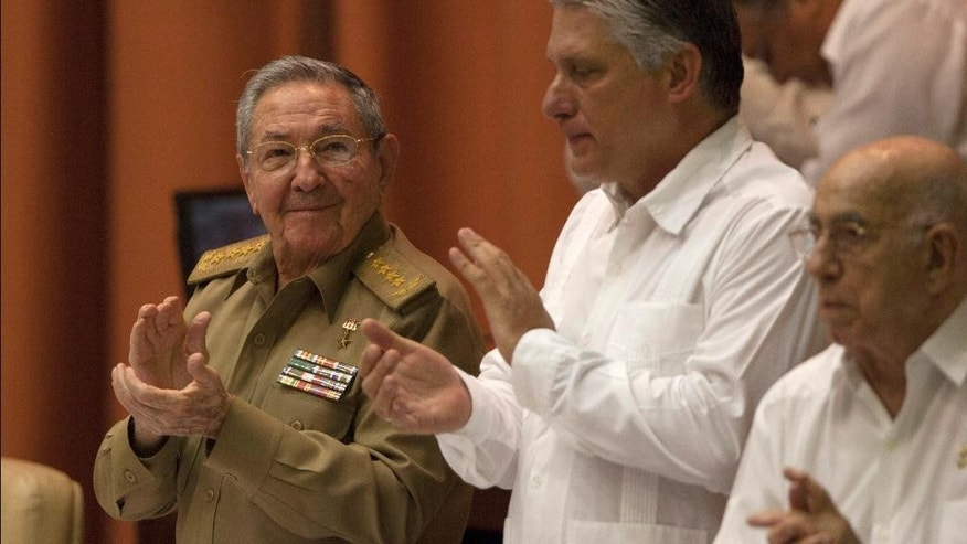 Cuba's President Raul Castro, left, applauds alongside Vice President Miguel Diaz-Canel, center, and Vice President Jose Ramon Machado Ventura during a National Assembly session in Havana, Cuba, Wednesday, July 15, 2015. State-run website Cubadebate reports that the body is considering a final budget report for 2014 and the status of Cuba's economic plan over the first half of this year. (AP Photo/Ismael Francisco, Cubadebate)