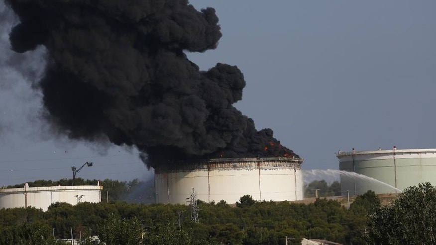 The smoke spreads in the sky from a fire in a tank of the U.S. Lyondellbasell chemicals group refinery, in Berre l'Etang, southern France, Tuesday, July 14, 2015. Two parallel explosions have rocked tanks at a chemical plant near Marseille Provence Airport . Authorities have launched an inquiry into the incident which occurred Tuesday morning as the country began celebrations for its national Bastille Day. Some 120 firefighter and 50 vehicles have been deployed to the petrochemical site, LyondellBasell, and air quality authorities are assessing if the fumes pose a threat to the quality of the air in the surrounding areas. There have been no reports of casualities.(AP Photo/Stringer)