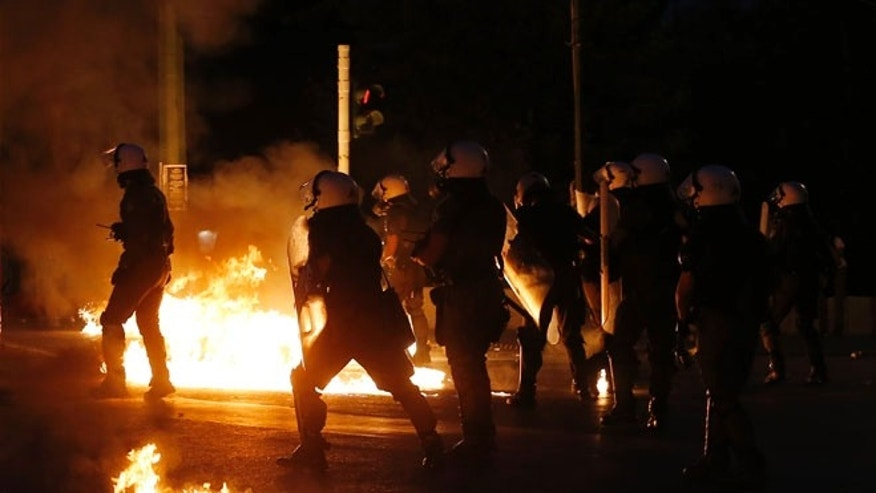 Riot police try to avoid petrol bombs thrown by anti-austerity protesters.