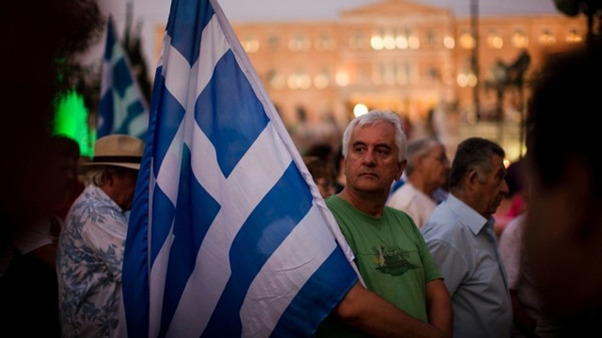 July 14, 2015: Demonstrators gather near the Greek Parliament during a rally against the government's agreement with its creditors in Athens. The eurozone's top official says it's not easy to find a way to get Greece a short-term cash infusion that will help it meet upcoming debt repayments. (AP Photo/Emilio Morenatti)