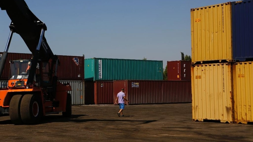 In this photo taken on Thursday, July 9, 2015 a worker walks between containers at the industrial zone of Aspropyrgos, western Athens. Imports in Greece have been hammered in the two weeks and more since strict capital controls were imposed. Business owners are warning that shortages of basic goods such as food will begin appearing if the situation isn't resolved and banks aren't reopened. (AP Photo/Petros Karadjias)