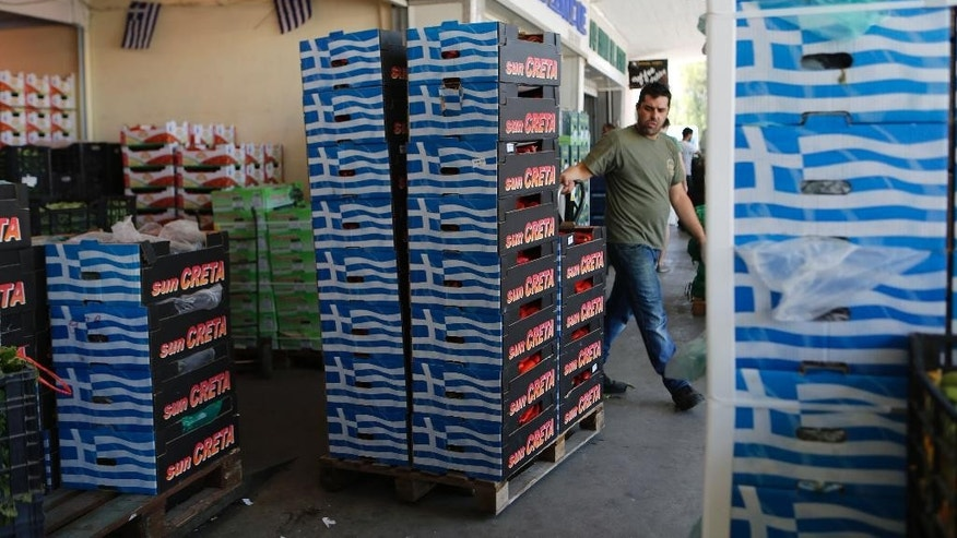 In this photo taken on Thursday, July 9, 2015 a worker pulls a trolley with peppers at the central fresh fruit and vegetable market in Athens. The country's economy is on its knees after weeks of political brinkmanship, uncertainty and bank closures battered companies and brought everyday business to a standstill. And new economic measures meant to secure the bailout are forecast to put the country, which has just emerged from six years of economic crisis, back into recession.  (AP Photo/Petros Karadjias)