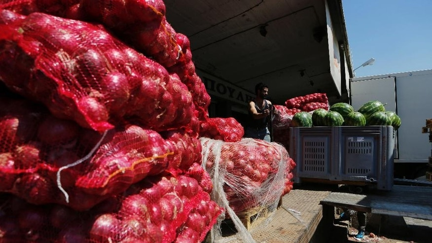 In this photo taken on Thursday, July 9, 2015 a worker pushes a trolley with onions and water melons at the central fresh fruit and vegetable market in Athens. Imports in Greece have been hammered in the two weeks and more since strict capital controls were imposed. Business owners are warning that shortages of basic goods such as food will begin appearing if the situation isn't resolved and banks aren't reopened. (AP Photo/Petros Karadjias)