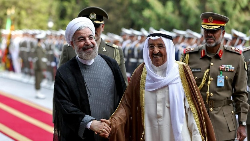 FILE - In this June 1, 2014, file photo, Kuwait's emir, Sheikh Sabah Al Ahmad Al Sabah, right, shakes hands with Iranian President Hassan Rouhani during a reception ceremony at the Saadabad Palace in Tehran, Iran. The emir of Kuwait, on Iran's nuclear deal agreed on Tuesday, July 14, 2015, sent congratulations to Iran and expressed hope the agreement will contribute to regional security and stability. (AP Photo/Ebrahim Noroozi, File)