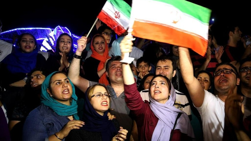 Jubilant Iranians sing and wave Iran flags during street celebrations following a landmark nuclear deal, in Tehran, Iran, Tuesday, July 14, 2015. After long, fractious negotiations, world powers and Iran struck an historic deal Tuesday to curb Iran's nuclear program in exchange for billions of dollars in relief from international sanctions - an agreement aimed at averting the threat of a nuclear-armed Iran and another U.S. military intervention in the Middle East. (AP Photo/Ebrahim Noroozi)