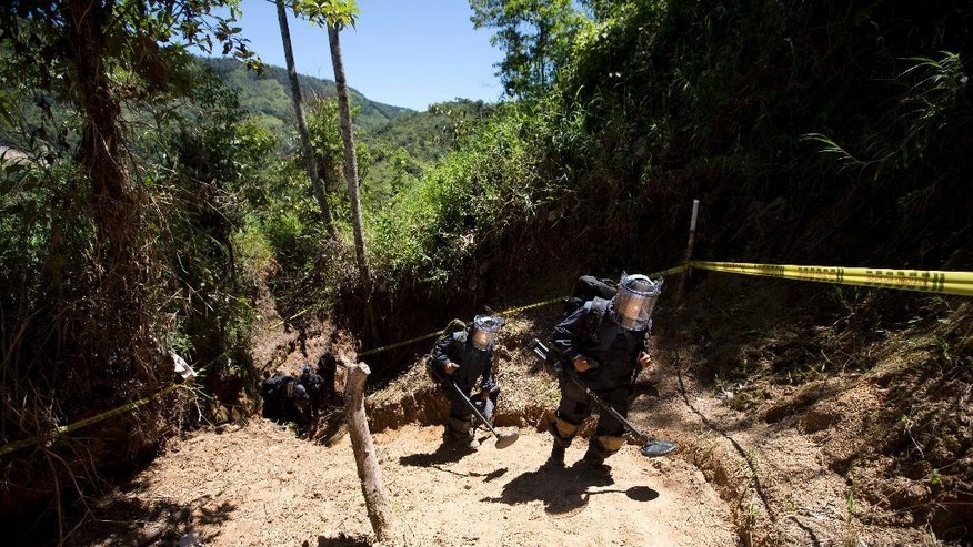 FILE - In this  June 24, 2015, file photo, soldiers leave an area after searching for land mines where farmers reported that rebels planted some in Granada, Colombia. The soldiers can search 13 meters per day, in an attempt to clear farms and roads so residents can return to their homes. (AP Photo/Fernando Vergara)