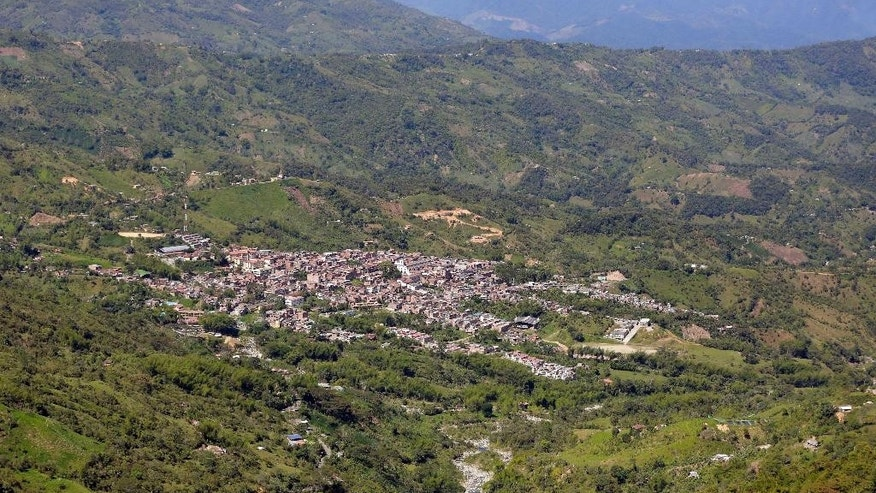 FILE - In this June 25, 2015, file photo, homes and businesses are nestled within the mountains surrounding Cocorna, Colombia. Soldiers are searching for and removing live land mines in rural areas like Cocorna, clearing farms and roads mined by rebels so residents can return to their homes. (AP Photo/Fernando Vergara, File)